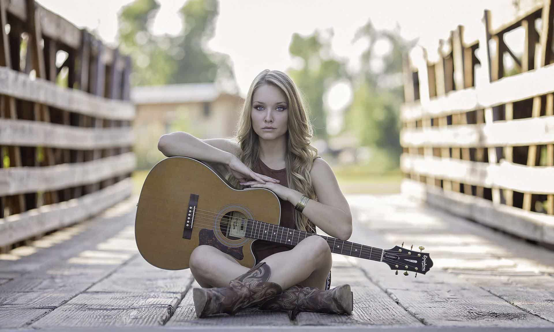 Country female singer sitting with guitar