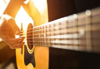 close up image of mans hand playing guitar