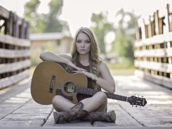 girl sitting cross legged holding acoustic guitar