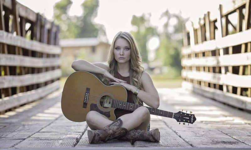 girl sitting cross legged holding acoustic guitar